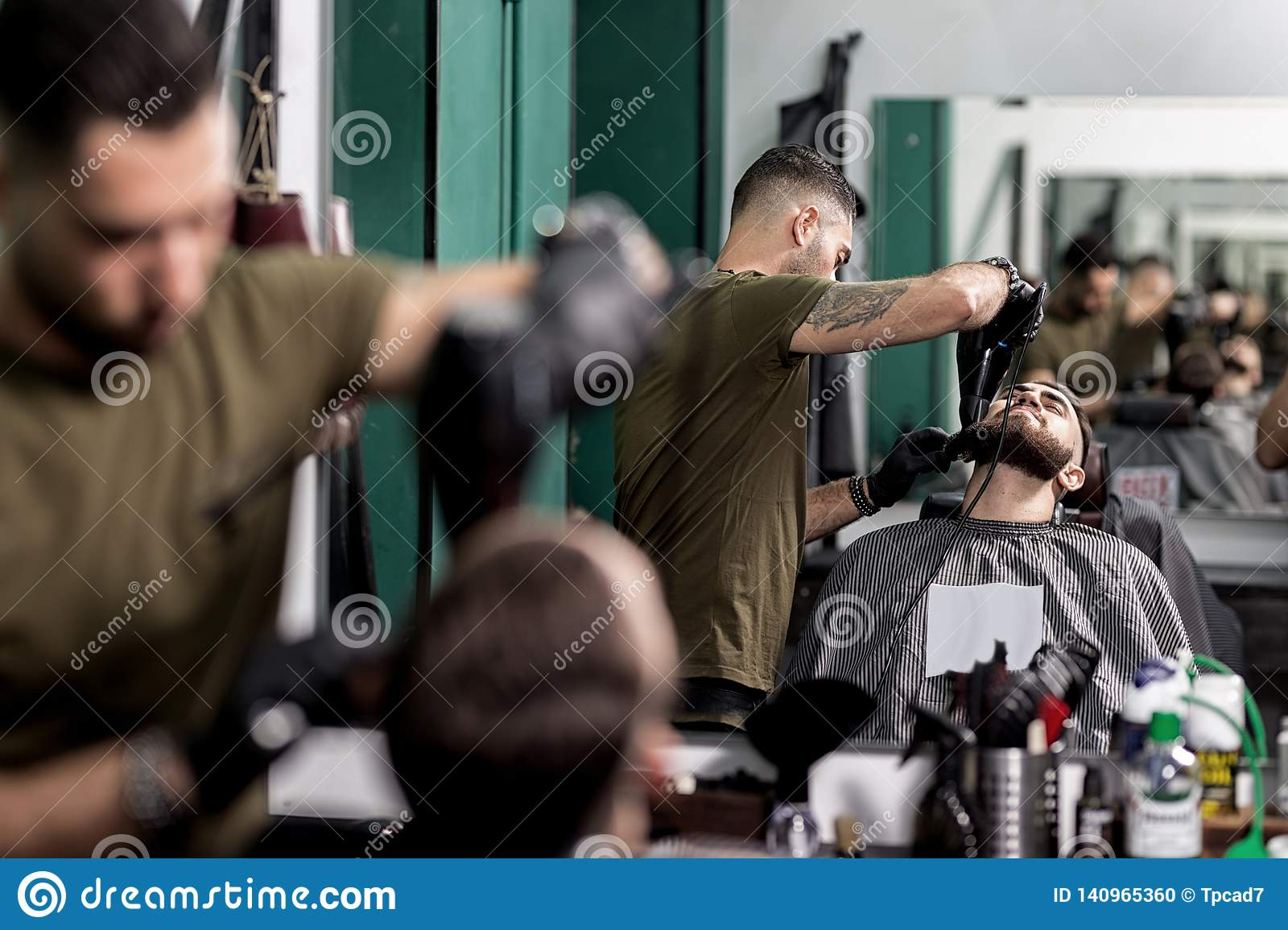 Brutal man with a beard sits in front of the mirror at a barbershop. Barber trims mens beard with scissors