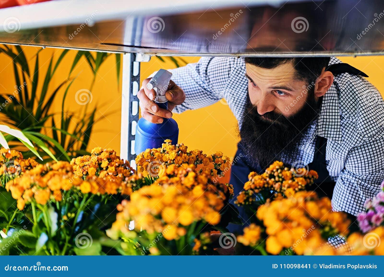 Brutal skäggig blommasäljare med tatueringar på hans armar i en flowe