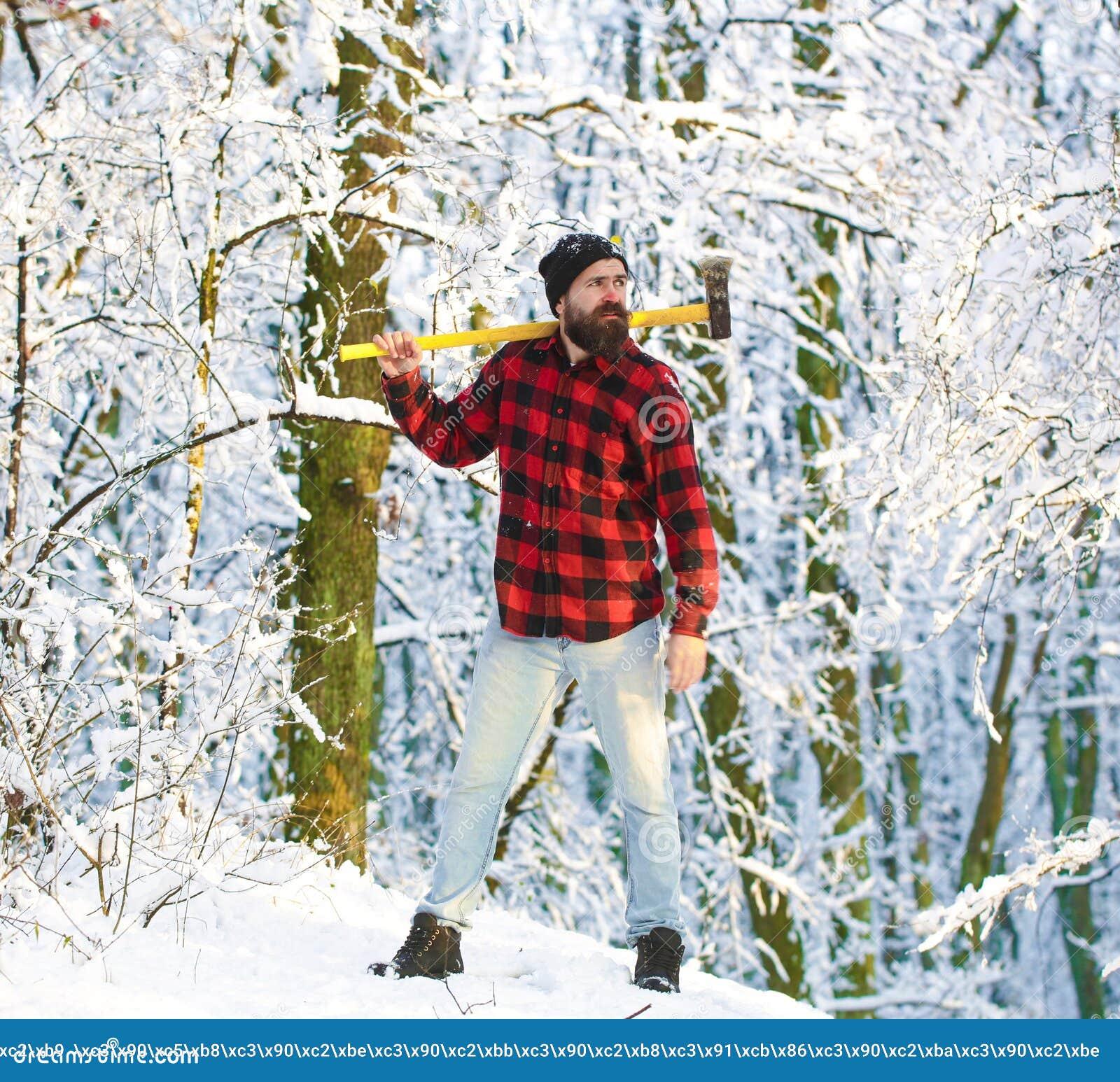 Brutal skäggig man för skogsarbetare med skägget och mustasch på vinterdag, snöig skogskogsarbetare i träna med en yxa