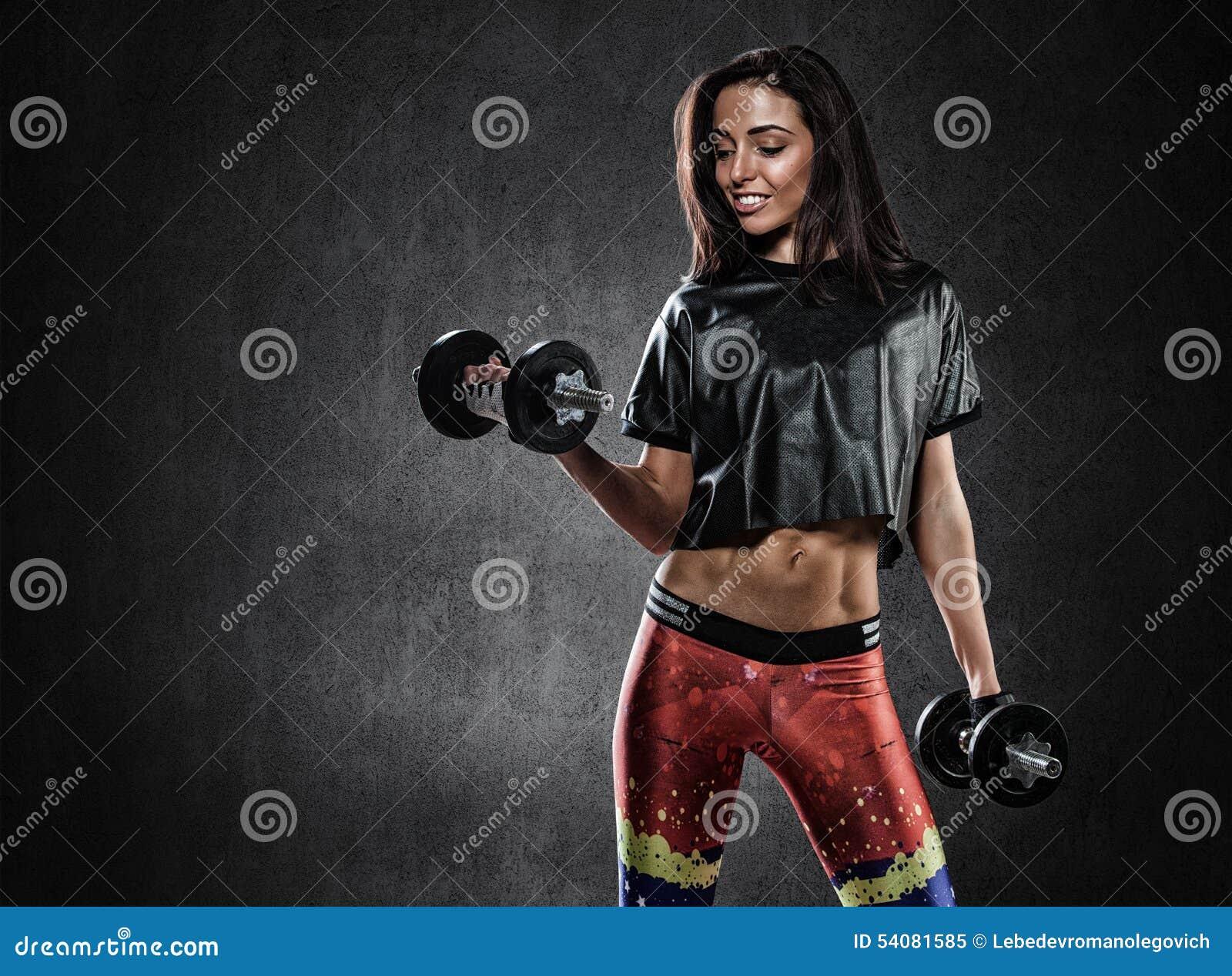 Brutale atletische vrouw die omhoog muscules met domoren pompen