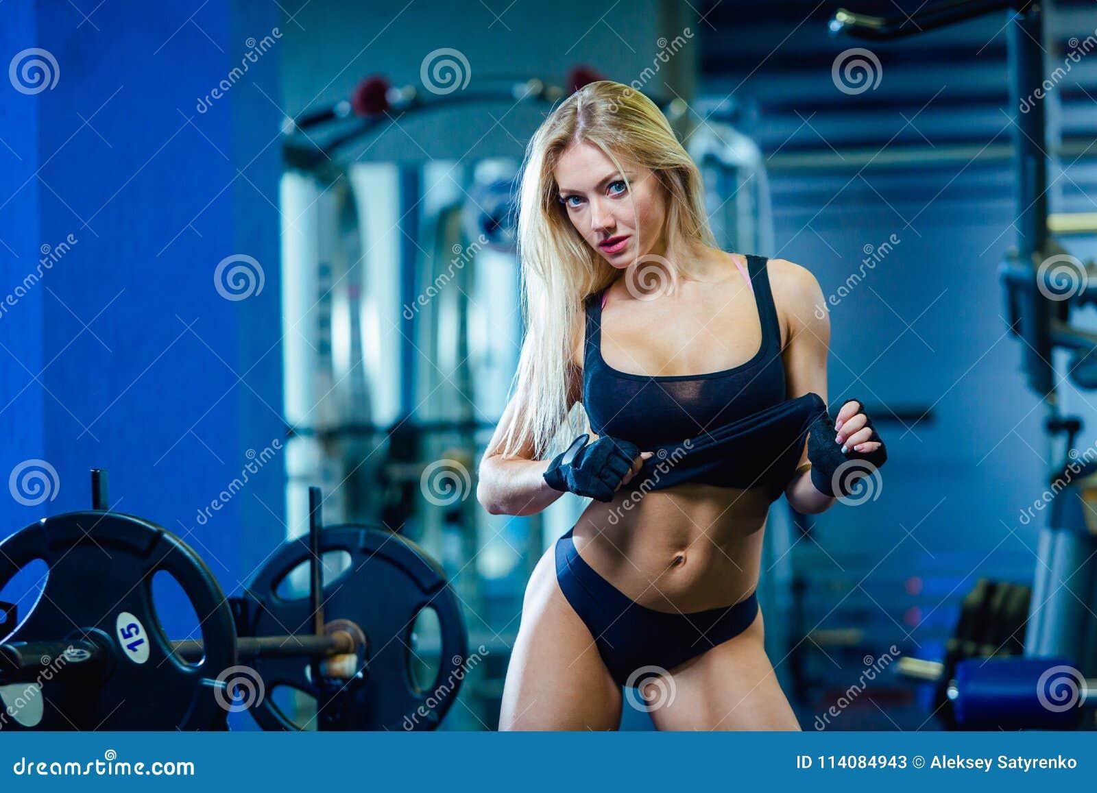 Brutale geschiktheids sexy vrouw met spier in de gymnastiek Sporten en fitness - concept gezonde levensstijl De vrouw van de gesc