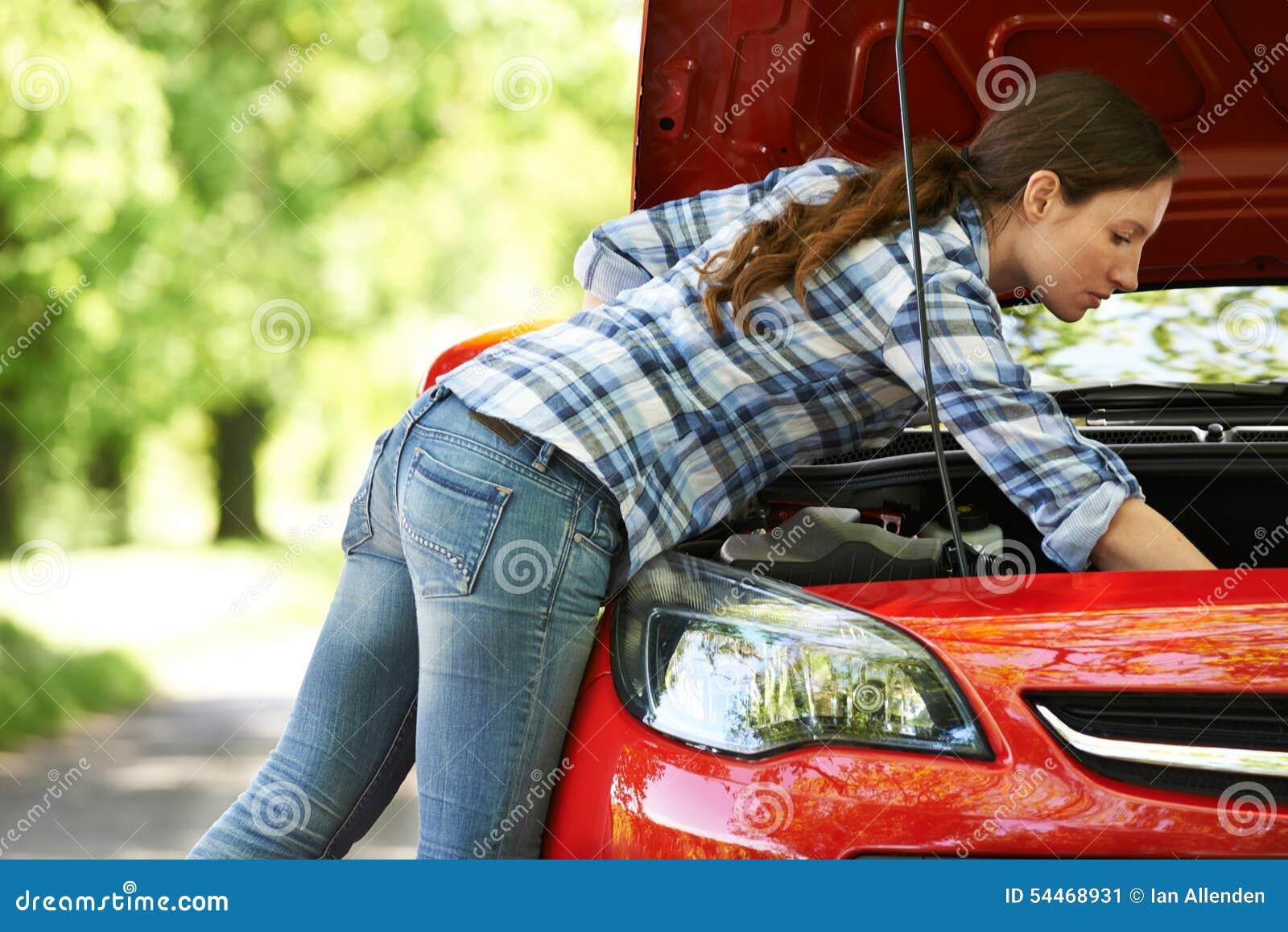 Bruten ner kvinnlig chaufför Looking Under Hood Of Car
