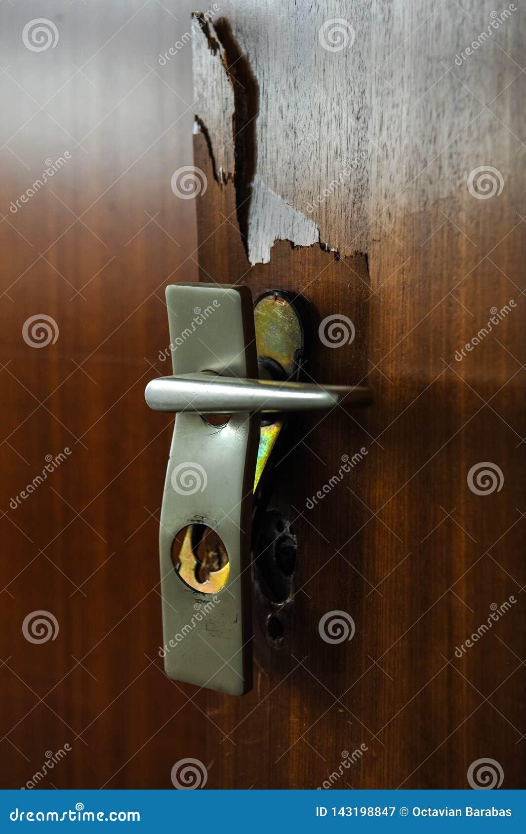 Brutet dörrlås med handtaget inom ett hus