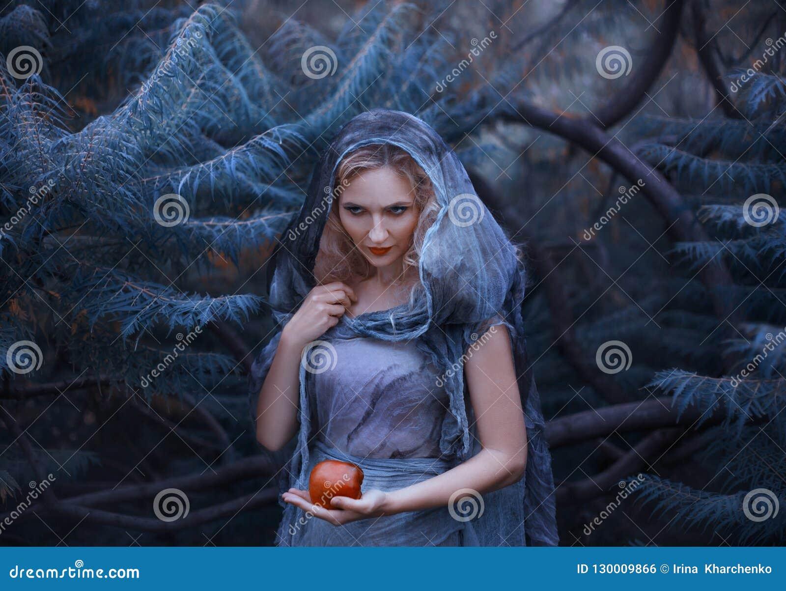 A bruxa astuto com cabelo encaracolado louro e o ódio em seus olhos, em um vestido de linho áspero velho com uma capa, mantêm env
