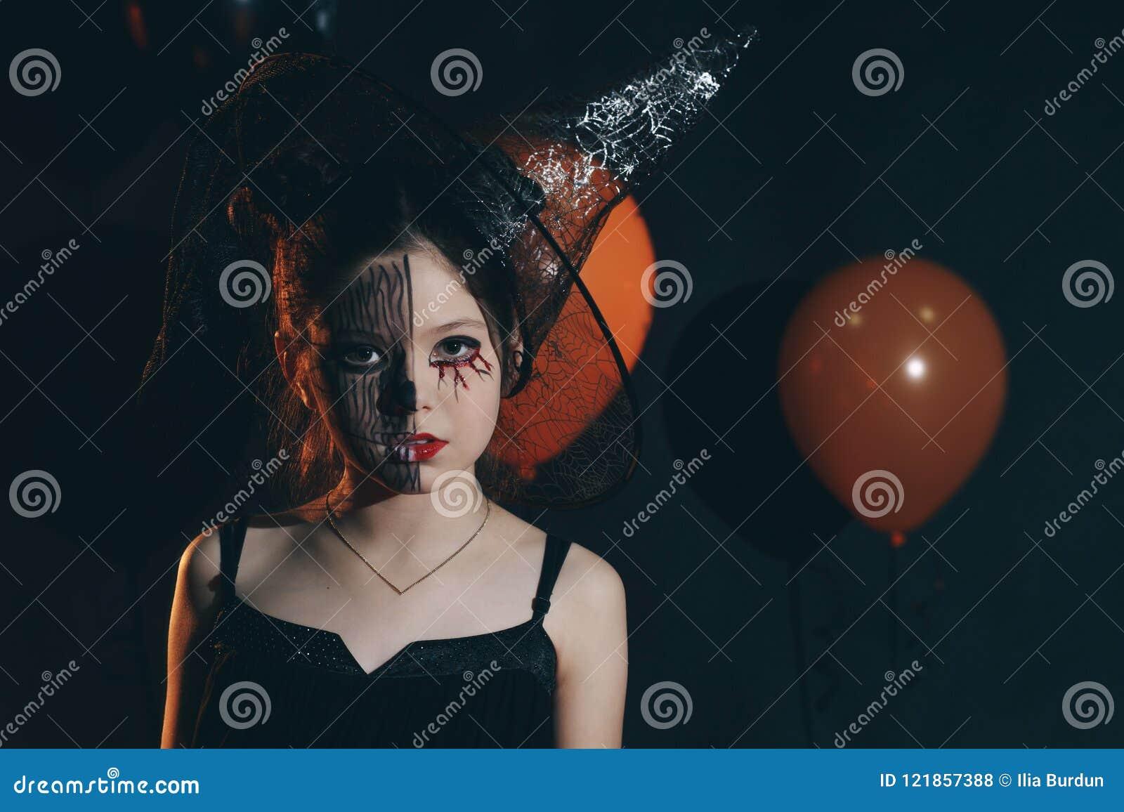 Bruxa pequena alegre bonito feliz de Dia das Bruxas com uma varinha e um livro mágicos dos períodos Menina da criança bonita no t