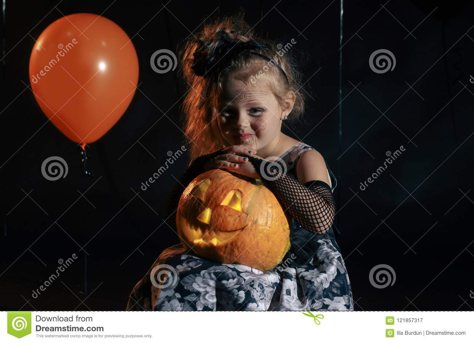 Bruxa pequena bonito feliz de Dia das Bruxas com uma abóbora