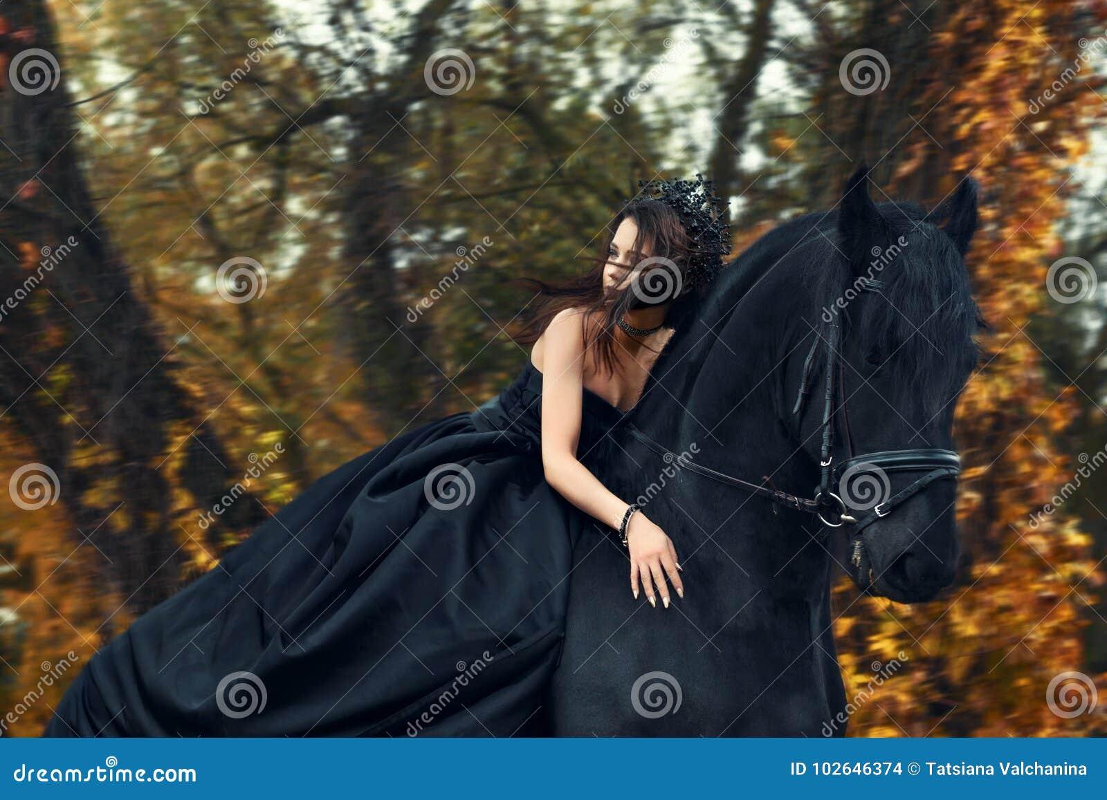 Bruxa preta da rainha da menina na equitação preta do vestido e da tiara horseback em um cavalo do frisão