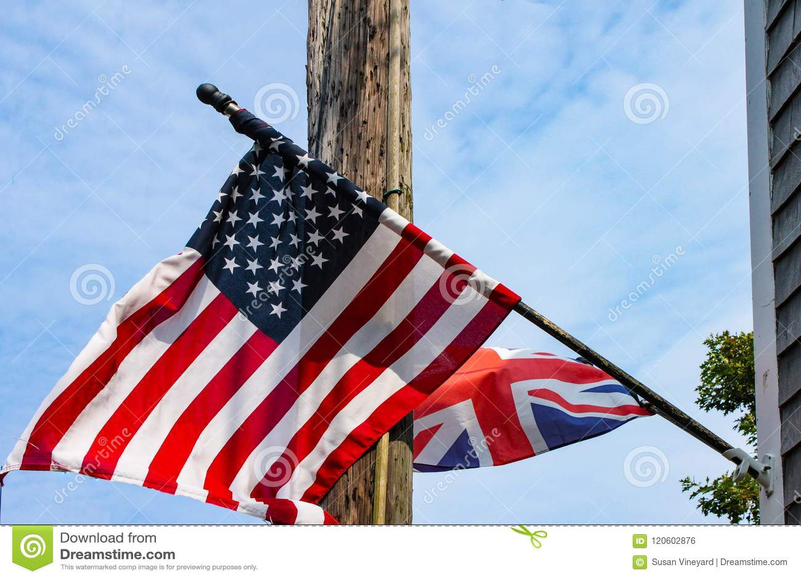 Brytyjski i flaga amerykańskie lata od wietrzejącego clapboard domu przed elektrycznym słupem i błękitnym chmurnym niebem