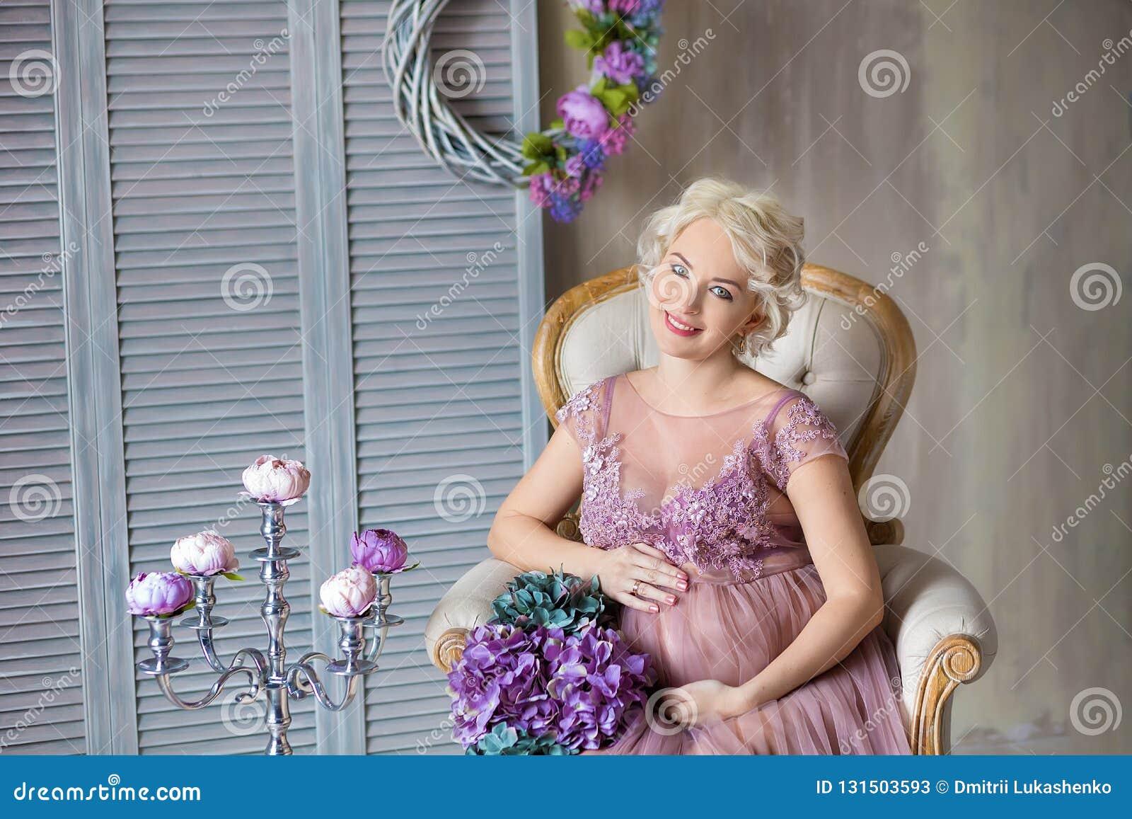 Brzemienność, macierzyństwo i szczęśliwy przyszłości matki pojęcie, - kobieta w ciąży w powiewnej fiołek sukni z bukietem kwitnie