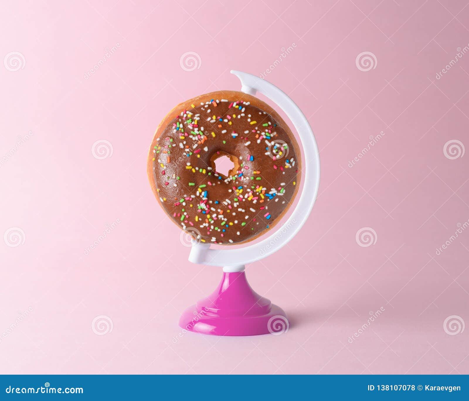 Buñuelo en un soporte del globo en fondo rosado en colores pastel Concepto mínimo