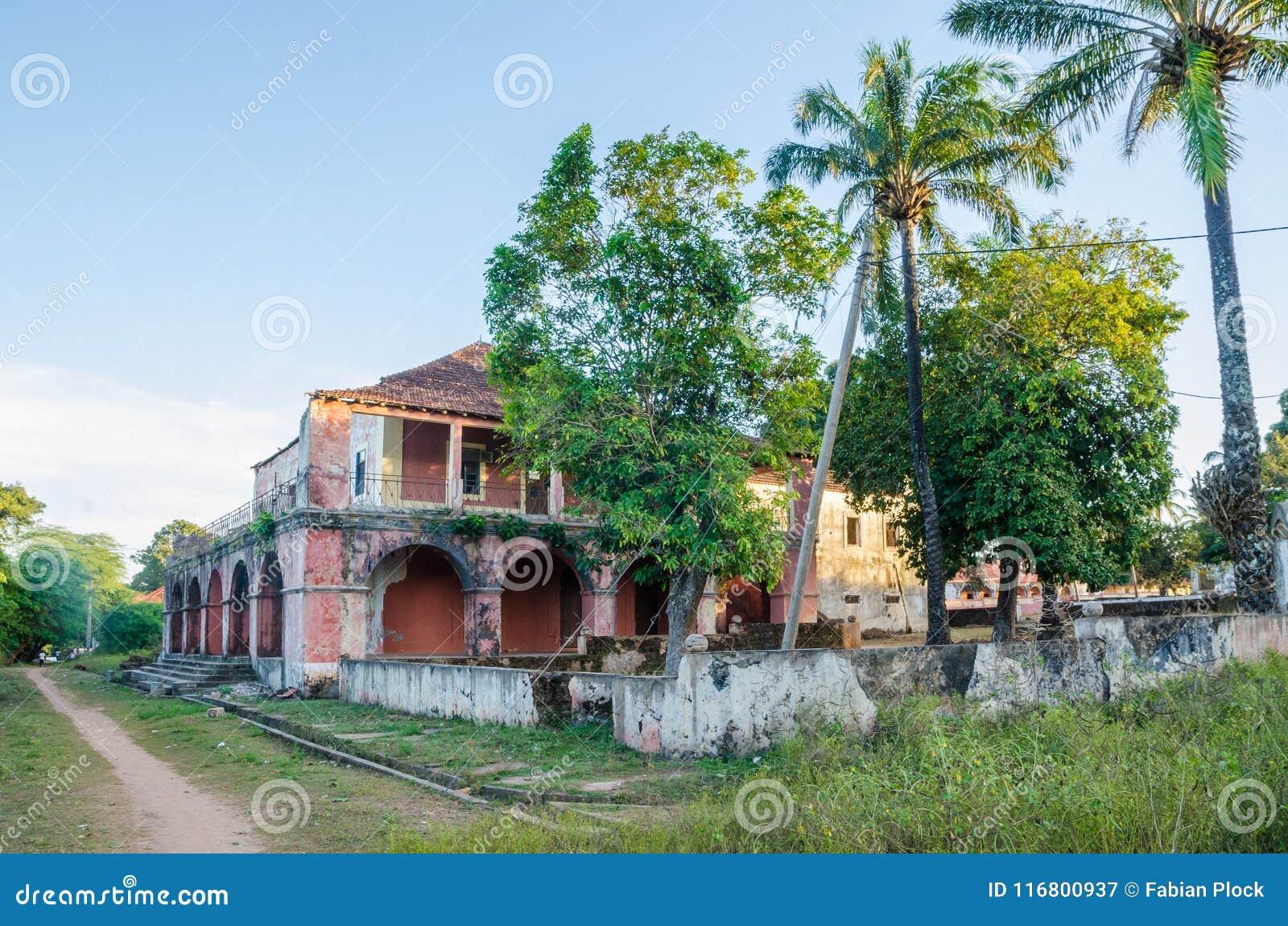 Bubaque, Guinea-Bissau - 11 dicembre 2013: Manson rovinato e vegetazione tropicale accanto al percorso della sporcizia