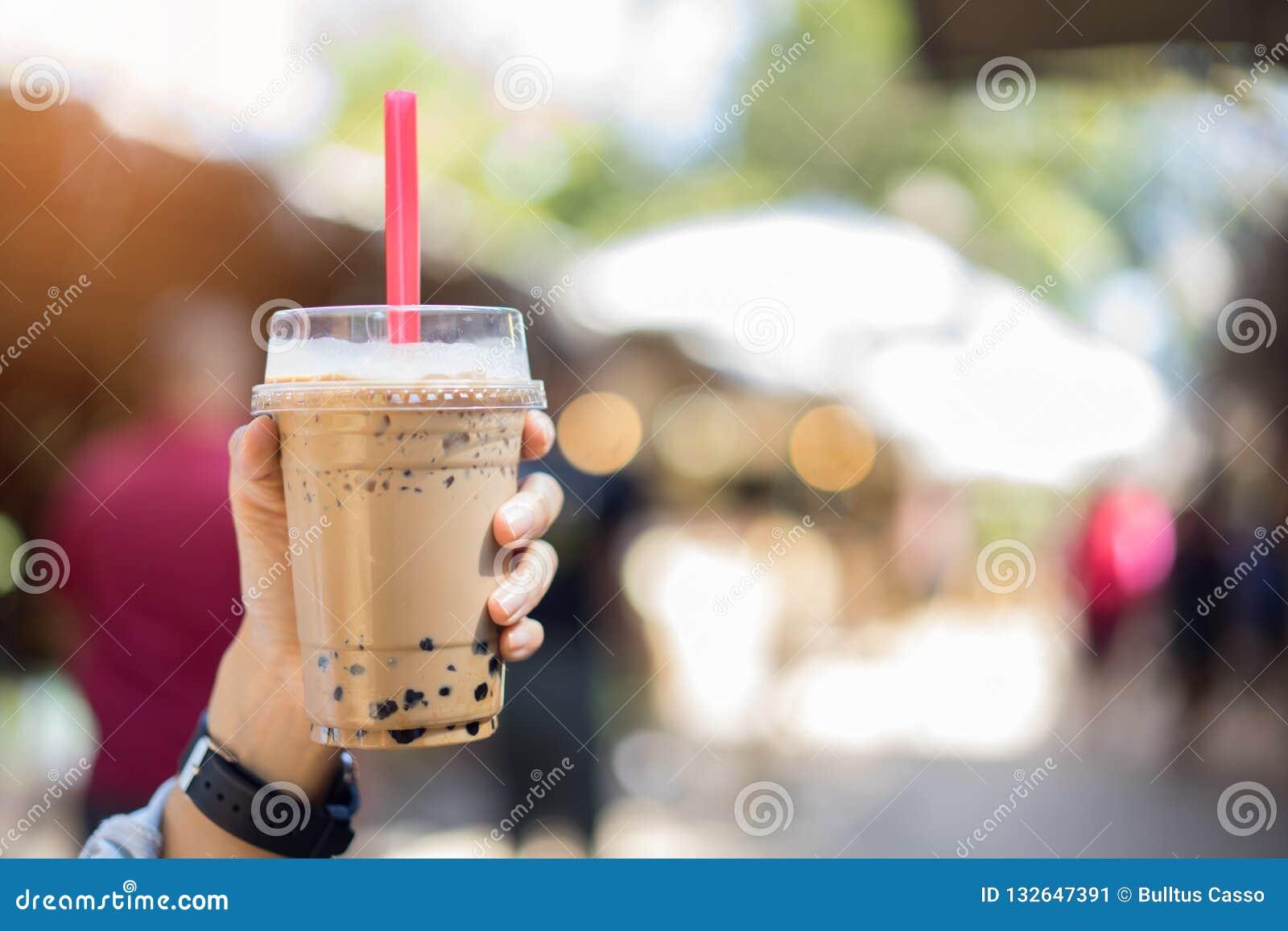 Bubblan mjölkar te i exponeringsglas i kvinnor räcker