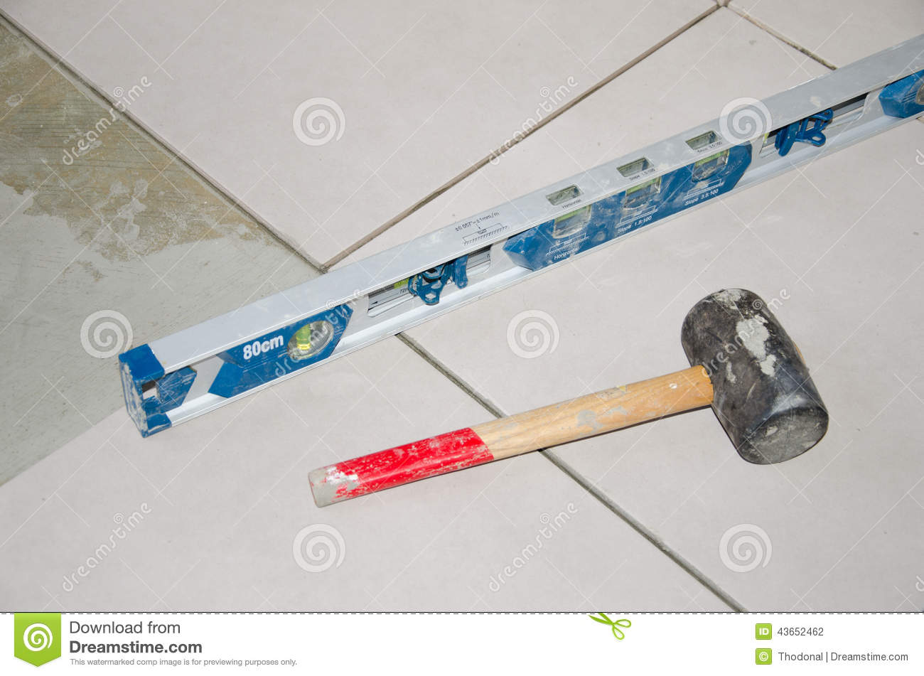 Bubble level and rubber mallet on a floor tiling