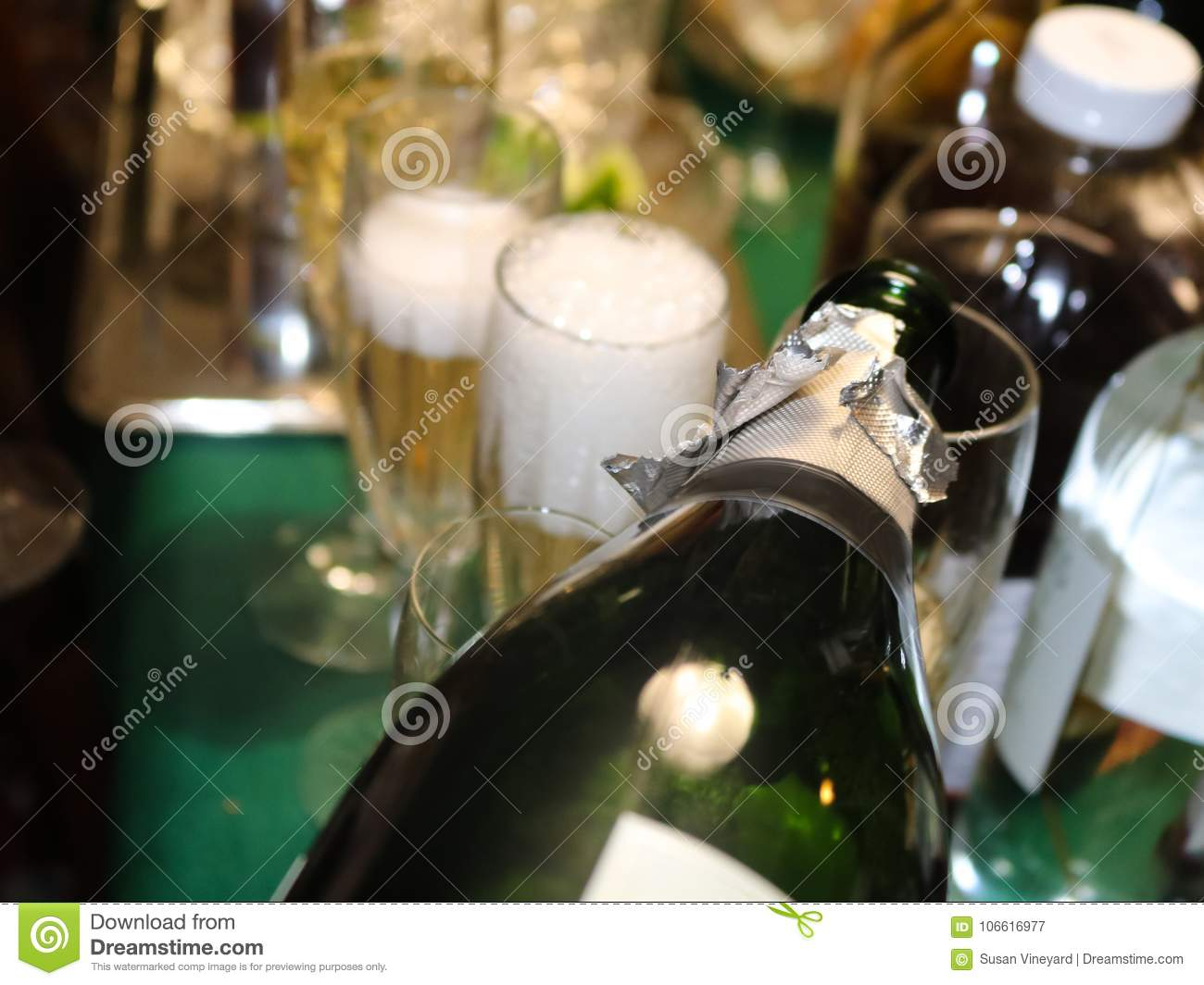 Bubbles coming off poured champagne in a foamy glass with surrounding bottle shapes and more champagne being poured