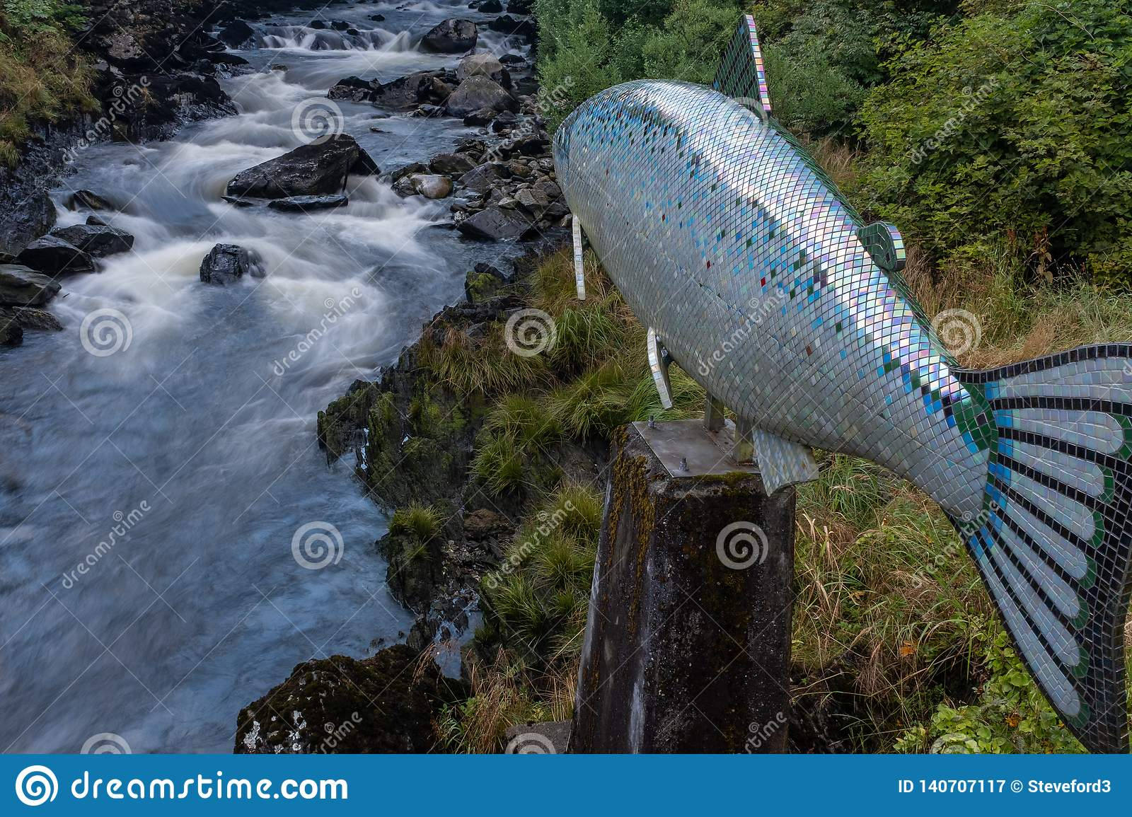 The bubbling Ketchikan Creek runs passed a sculpture of a salmon