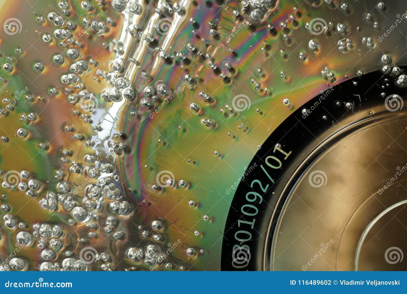 Bubblor på skadad CD yttersida Texturerad backgroun för makro abstrakt begrepp