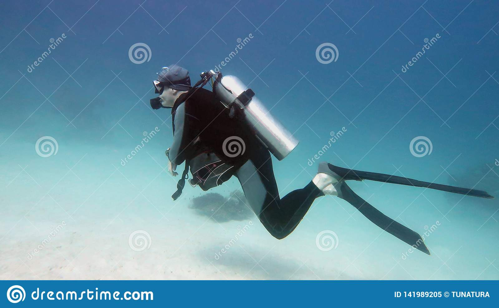 Buceador del hombre en el agua azul