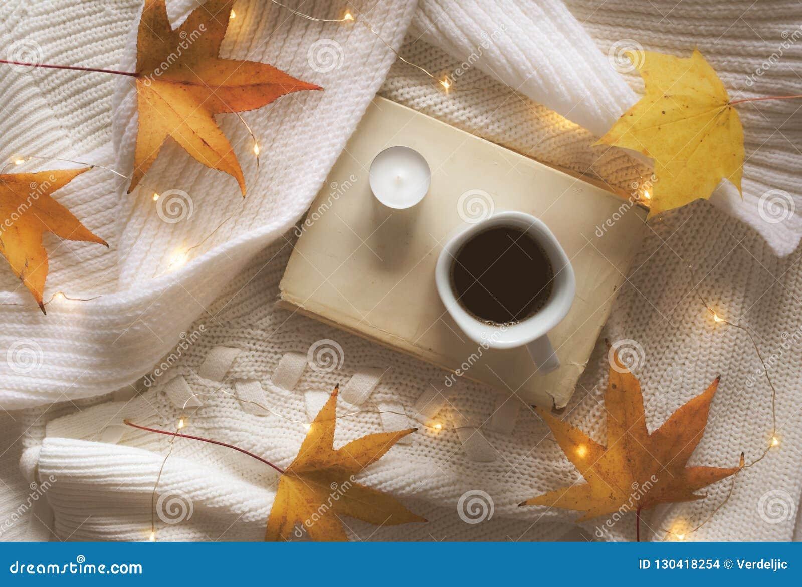 Buch, Kaffee, goldene Blätter, Kerze und Lichter auf einer weißen Strickjacke