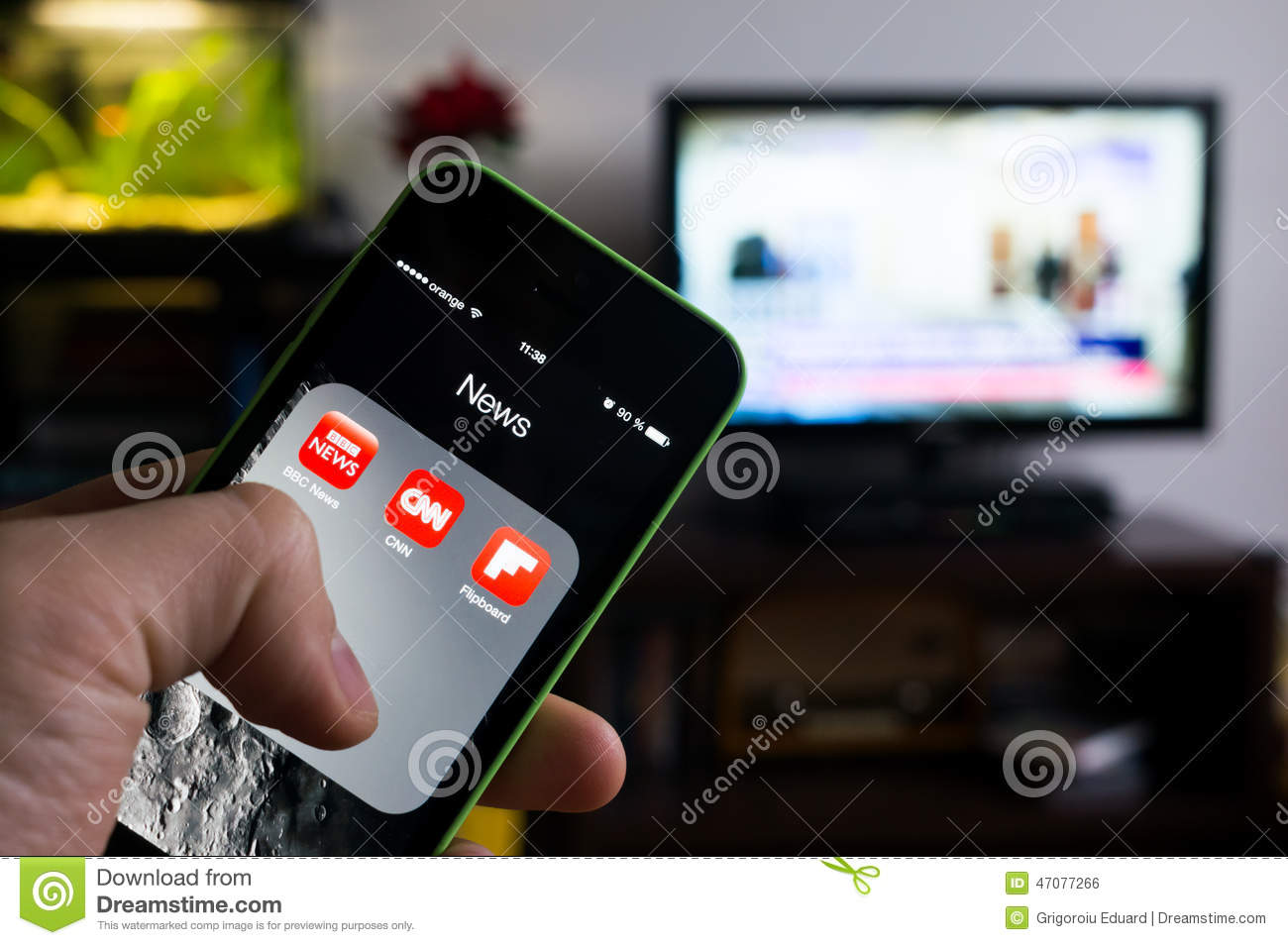 BUCHAREST, ROMANIA - NOVEMBER 21, 2014: Photo of hand holding an iphone with news apps on screen and tv set in the background with