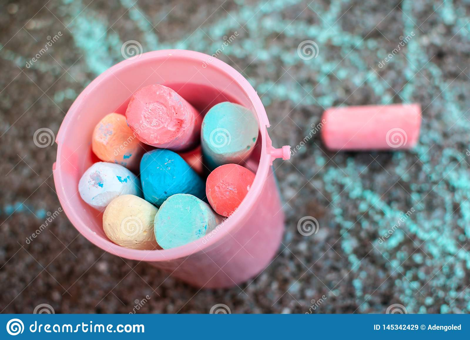 A bucket of colourful chalks against pavement full of scribbles. Toddler or child activity. Back to school.
