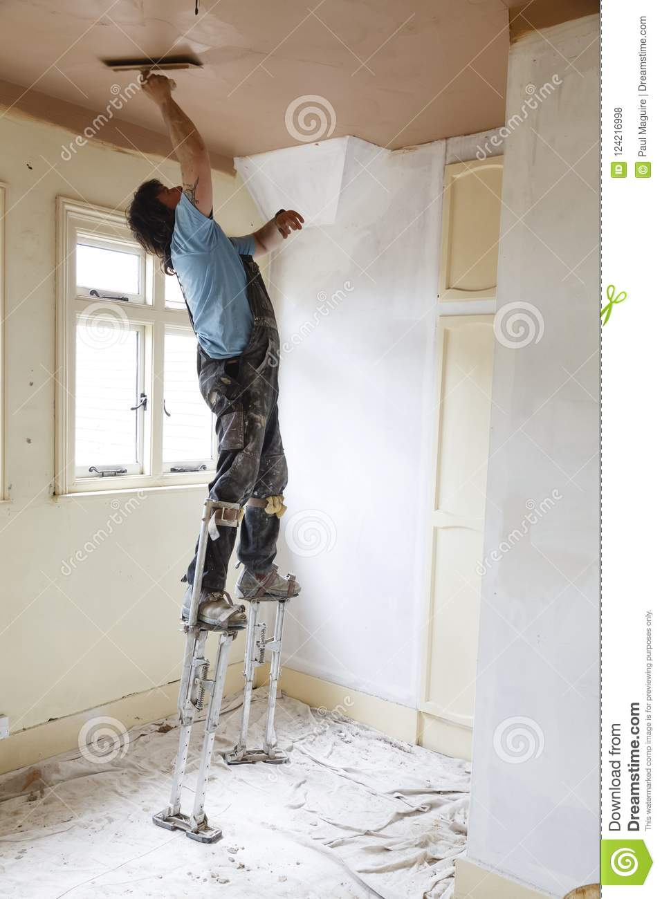 buckingham-uk-may-plasterer-skims-high-ceiling-whilst-standing-stilts-skilled-plasterer-can-work-far-more-quickly-124216998.jpg