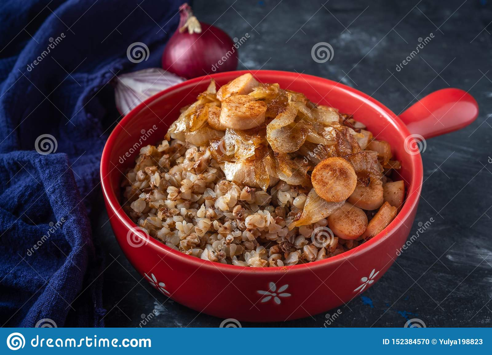 Buckwheat porridge with sausages and fried onions in a red pan on a dark background, copy space