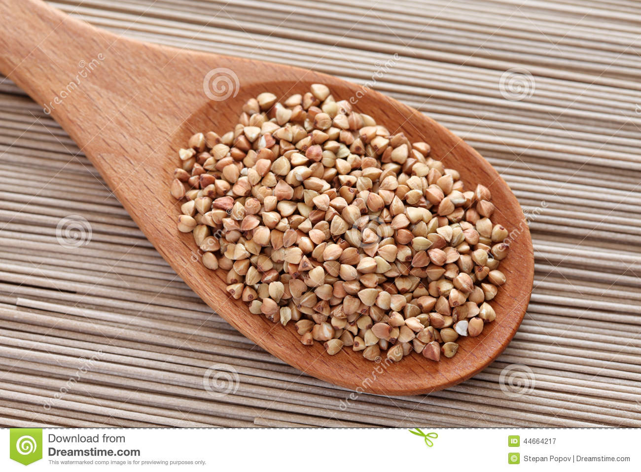 Buckwheat in a wooden spoon on soba noodles background