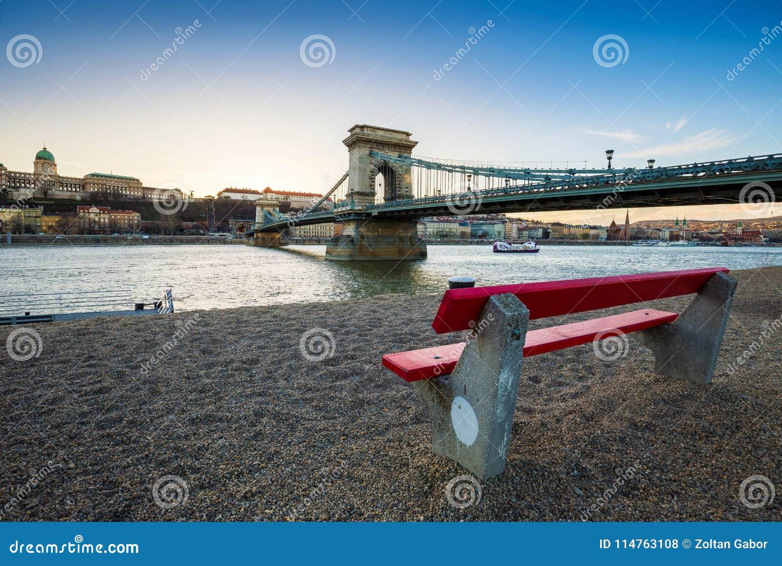 Budapest, Hongrie - banc rouge traditionnel à la rive avec le pont à chaînes de Szechenyi, Buda Castle Royal Palace