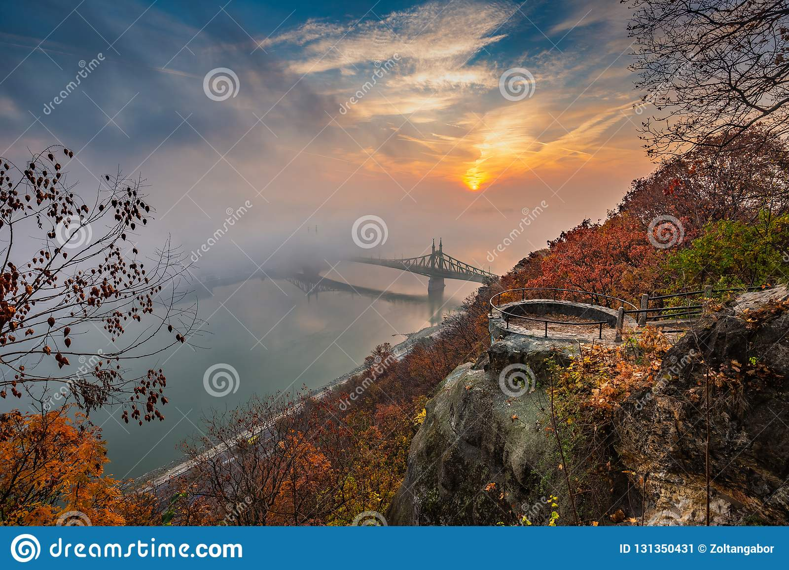 Budapest, Hungary - Lookout on Gellert Hill with Liberty Bridge Szabadsag Hid, fog over River Danube, colorful sky and clouds