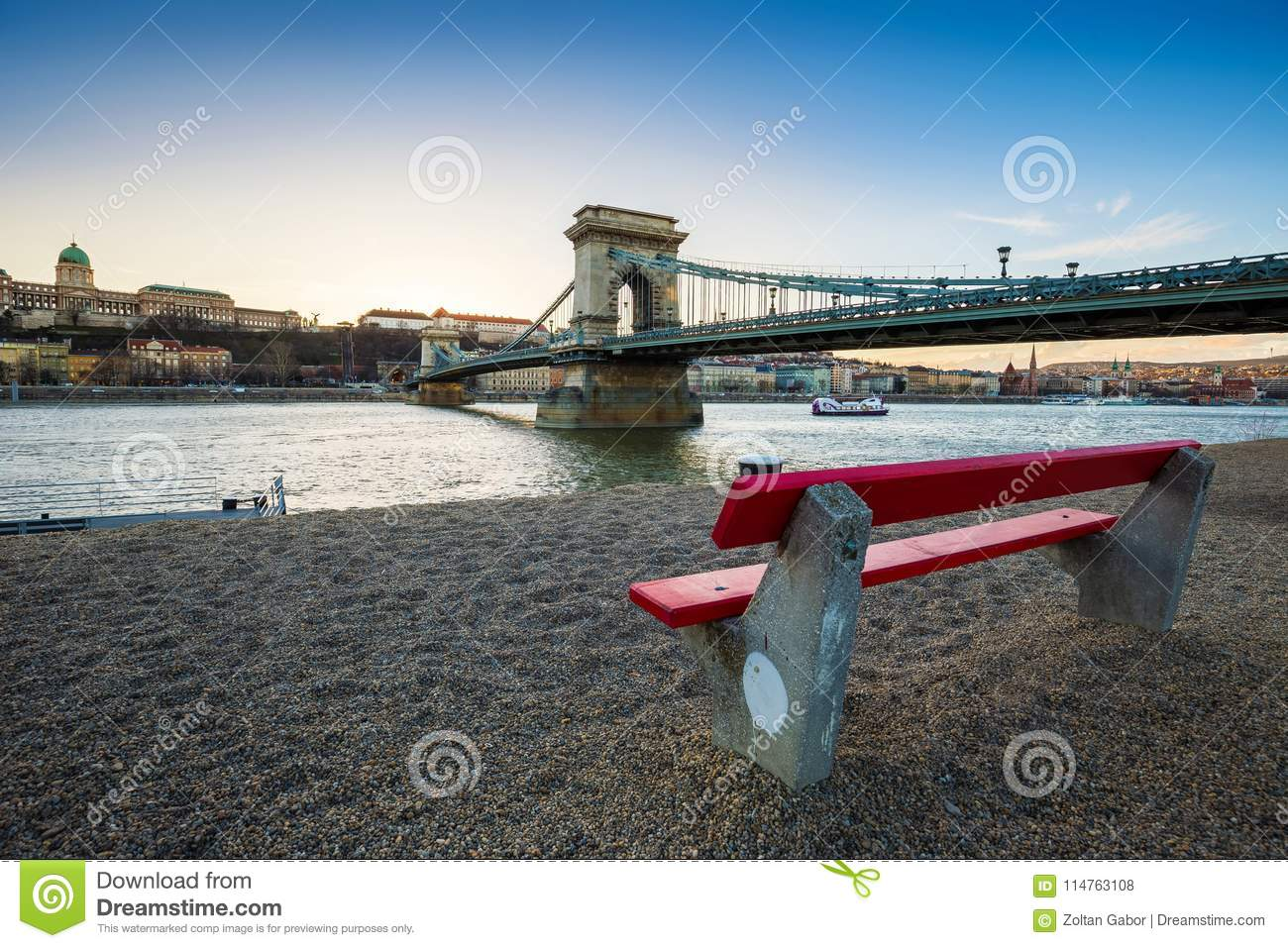 Budapest, Hungary - Traditional red bench at the riverside with Szechenyi Chain Bridge, Buda Castle Royal Palace