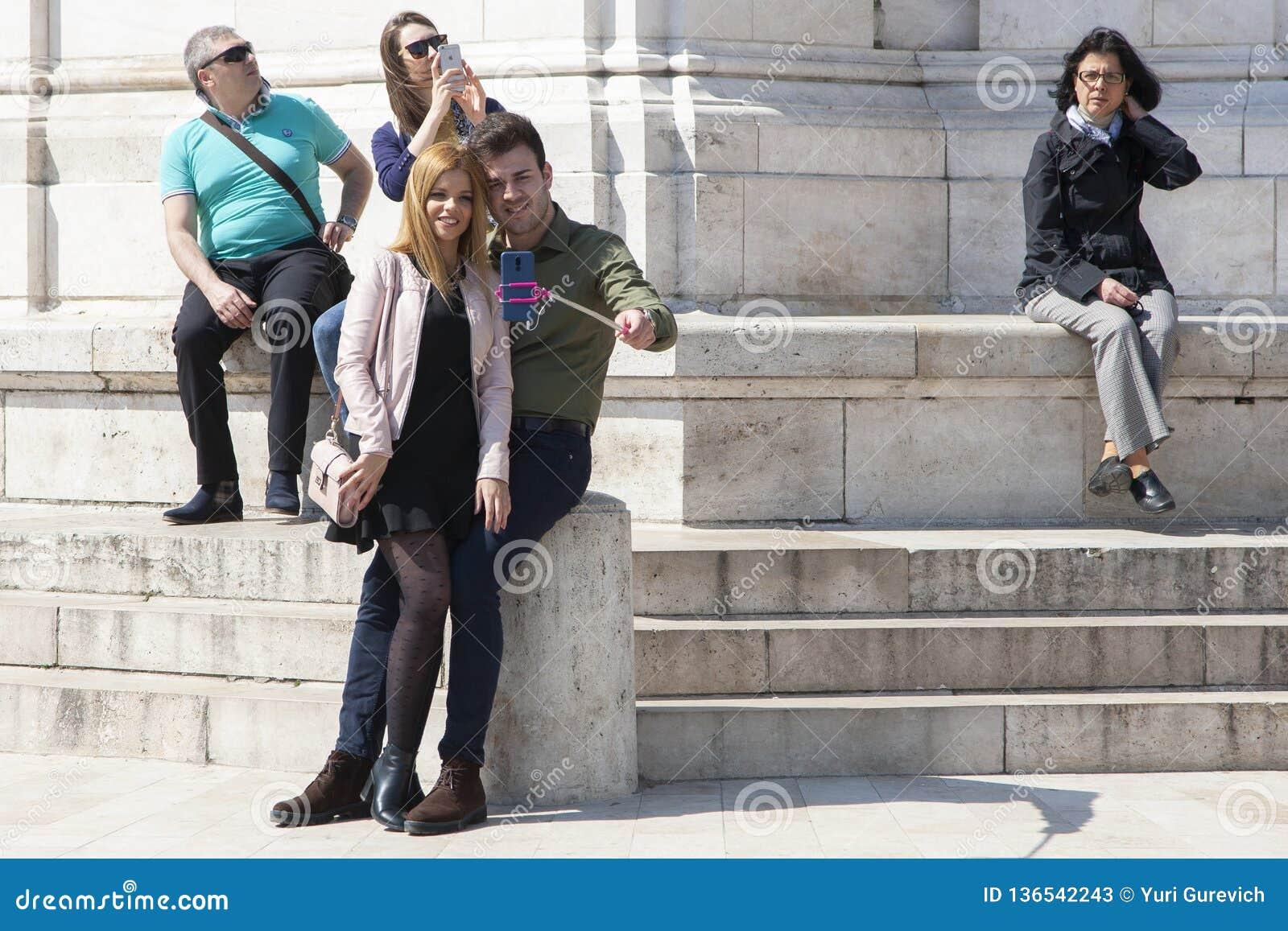 Budapest Ungern - April 8, 2018: par som tar selfie med en telefon och gör enfaldiga framsidor i gatan