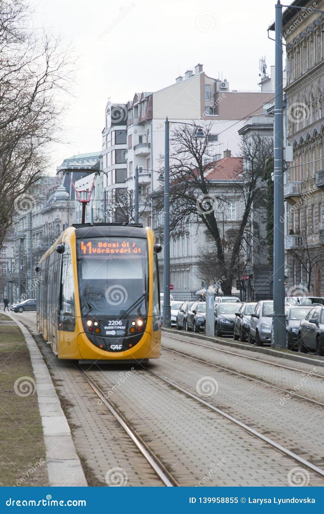 Budapest Ungern, Februari 13, 2019 Gula bilar av den Budapest spårvagnen ankommer på stoppet