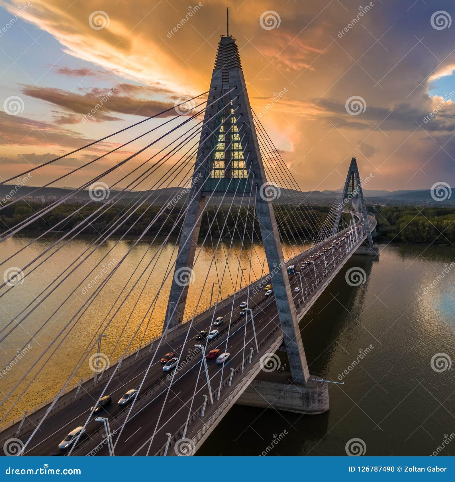 Budapest Ungern - Megyeri bro över flodDonau på solnedgången med tung trafik, härliga dramatiska moln