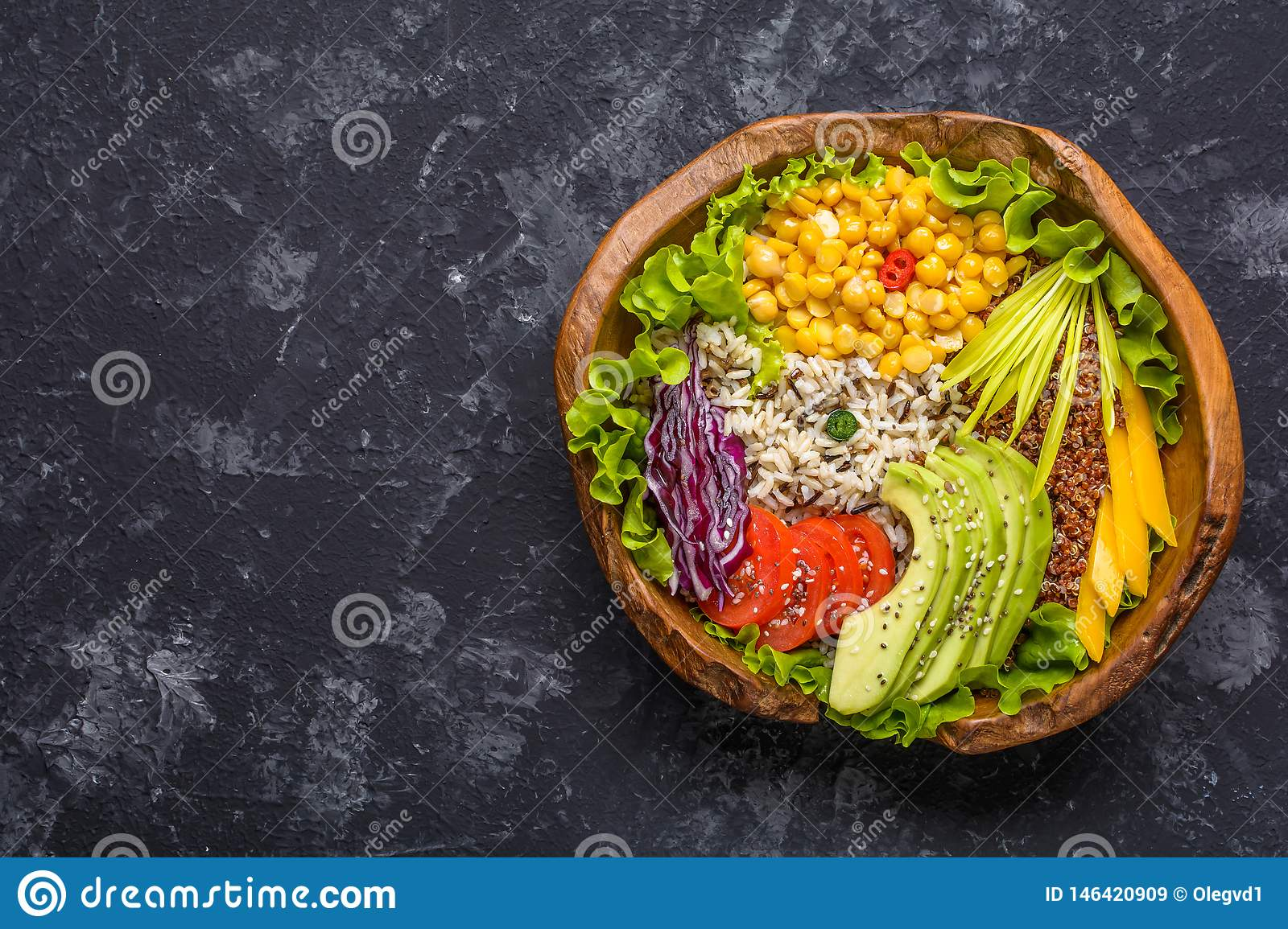 Buddha bowl with chickpea, avocado, wild rice, quinoa seeds, bell pepper, tomatoes, greens, cabbage, lettuce on dark stone table.