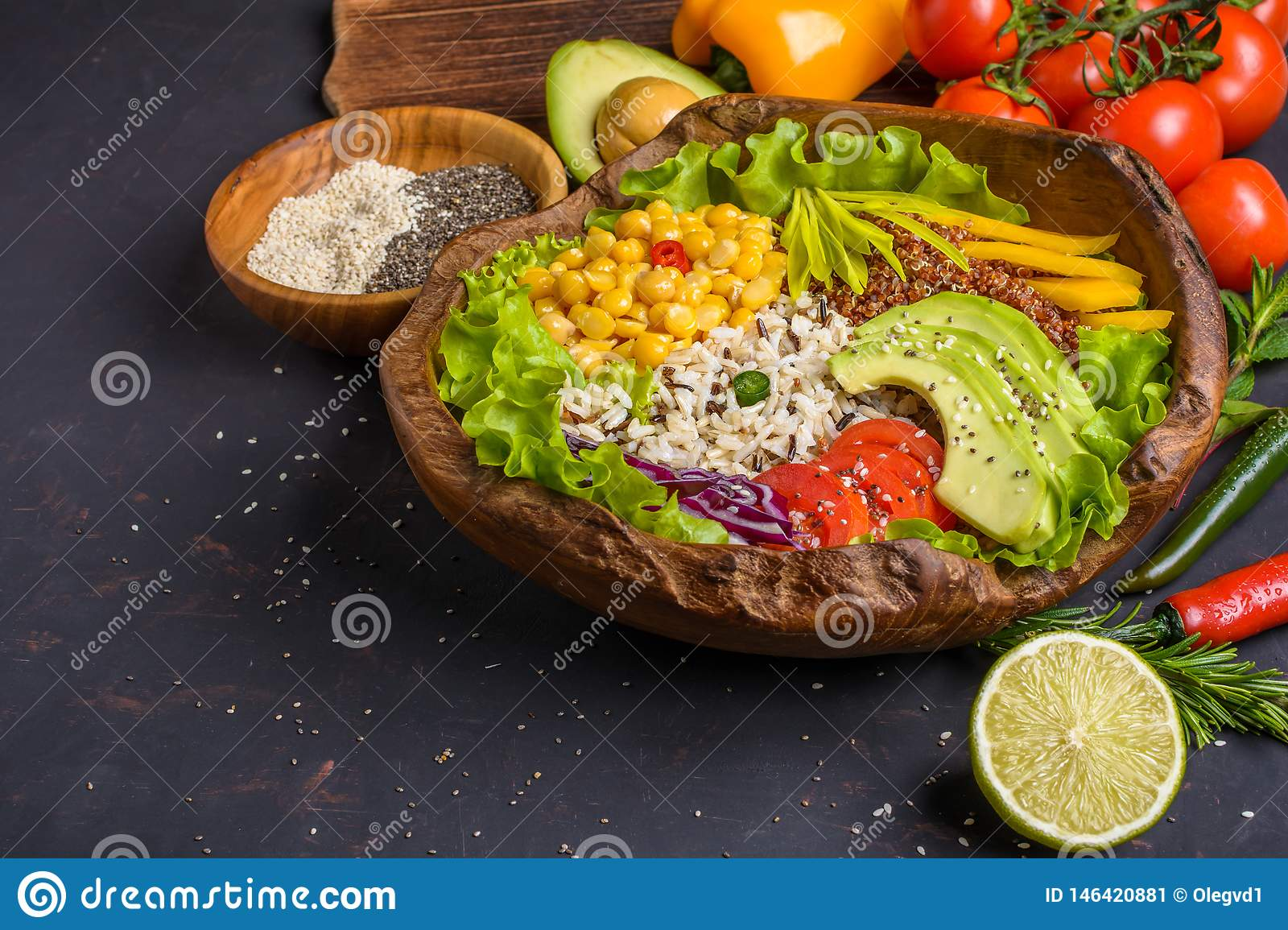 Buddha bowl with chickpea, avocado, wild rice, quinoa seeds, bell pepper, tomatoes, greens, cabbage, lettuce on dark stone table