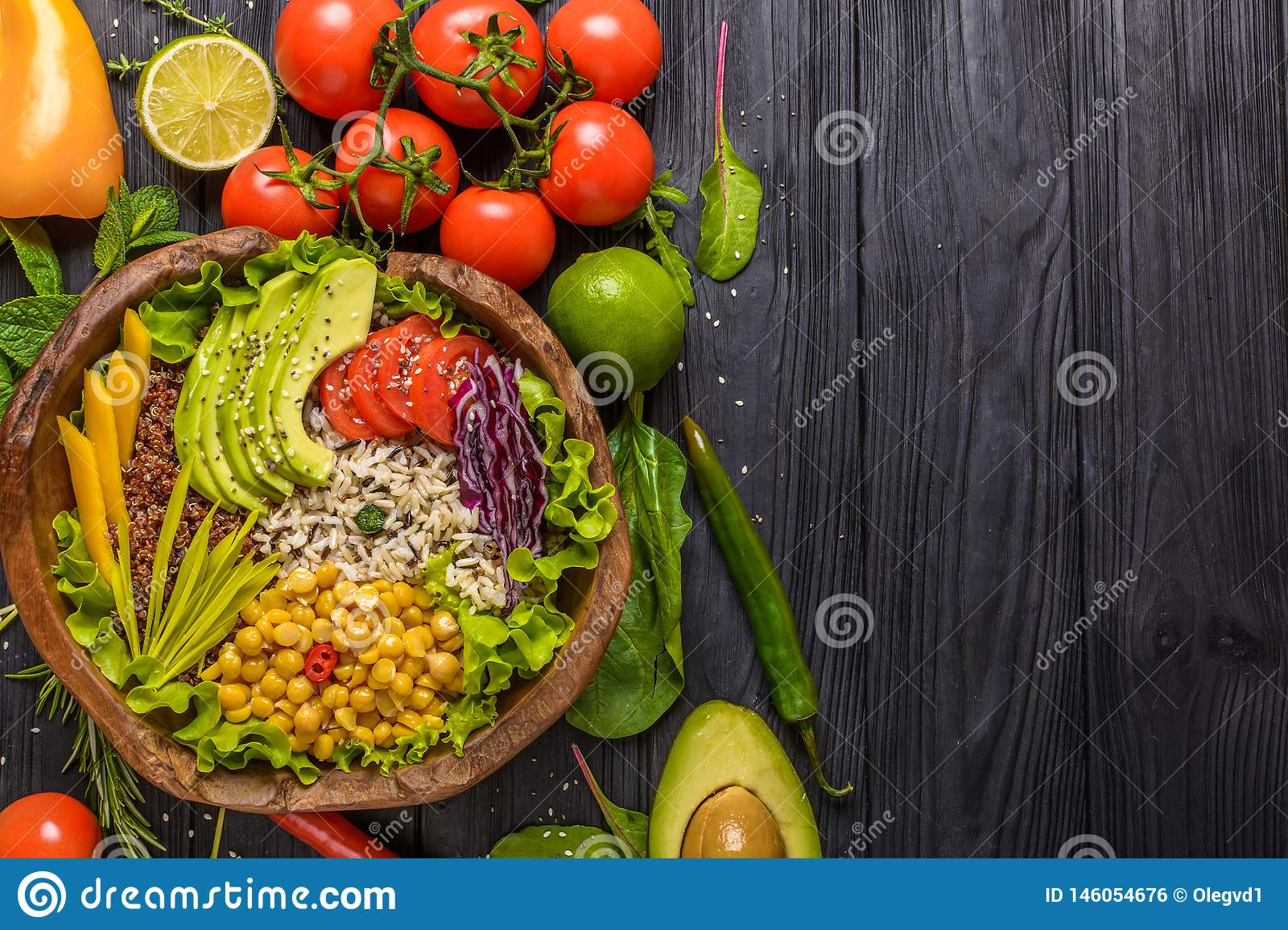 Buddha bowl with chickpea, avocado, wild rice, quinoa seeds, bell pepper, tomatoes, greens, cabbage, lettuce on old black wooden