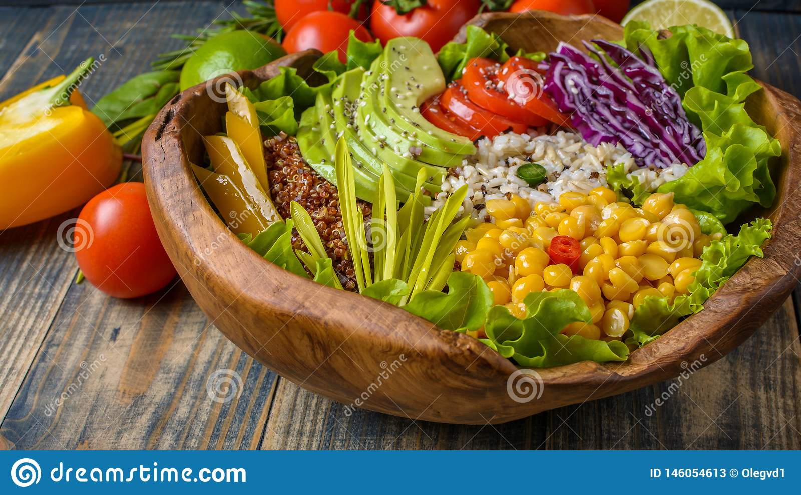 Buddha bowl with chickpea, avocado, wild rice, quinoa seeds, bell pepper, tomatoes, greens, cabbage, lettuce on old shabby wooden
