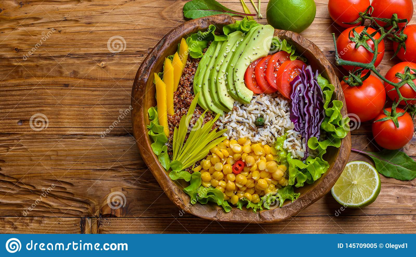 Buddha bowl with chickpea, avocado, wild rice, quinoa seeds, bell pepper, tomatoes, greens, cabbage, lettuce on old wooden table.