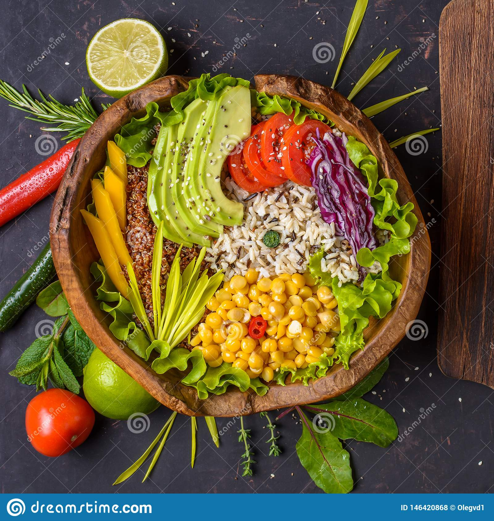Buddha bowl with chickpea, avocado, wild rice, quinoa seeds, bell pepper, tomatoes, greens, cabbage, lettuce on shabby dark stone
