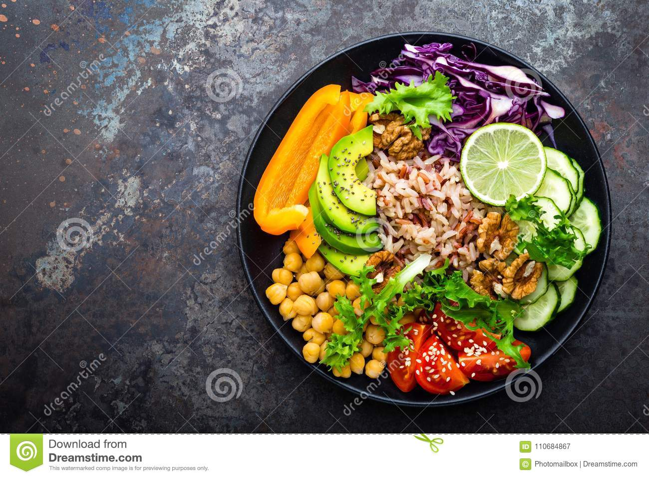 Buddha bowl dish with brown rice, avocado, pepper, tomato, cucumber, red cabbage, chickpea, fresh lettuce salad and walnuts. Healt
