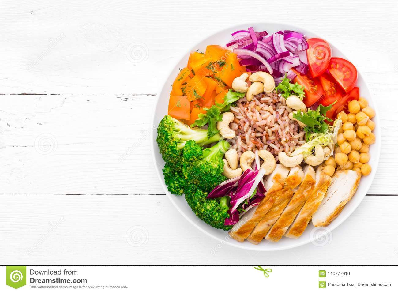 Buddha bowl dish with chicken fillet, brown rice, pepper, tomato, broccoli, onion, chickpea, fresh lettuce salad, cashew and walnu