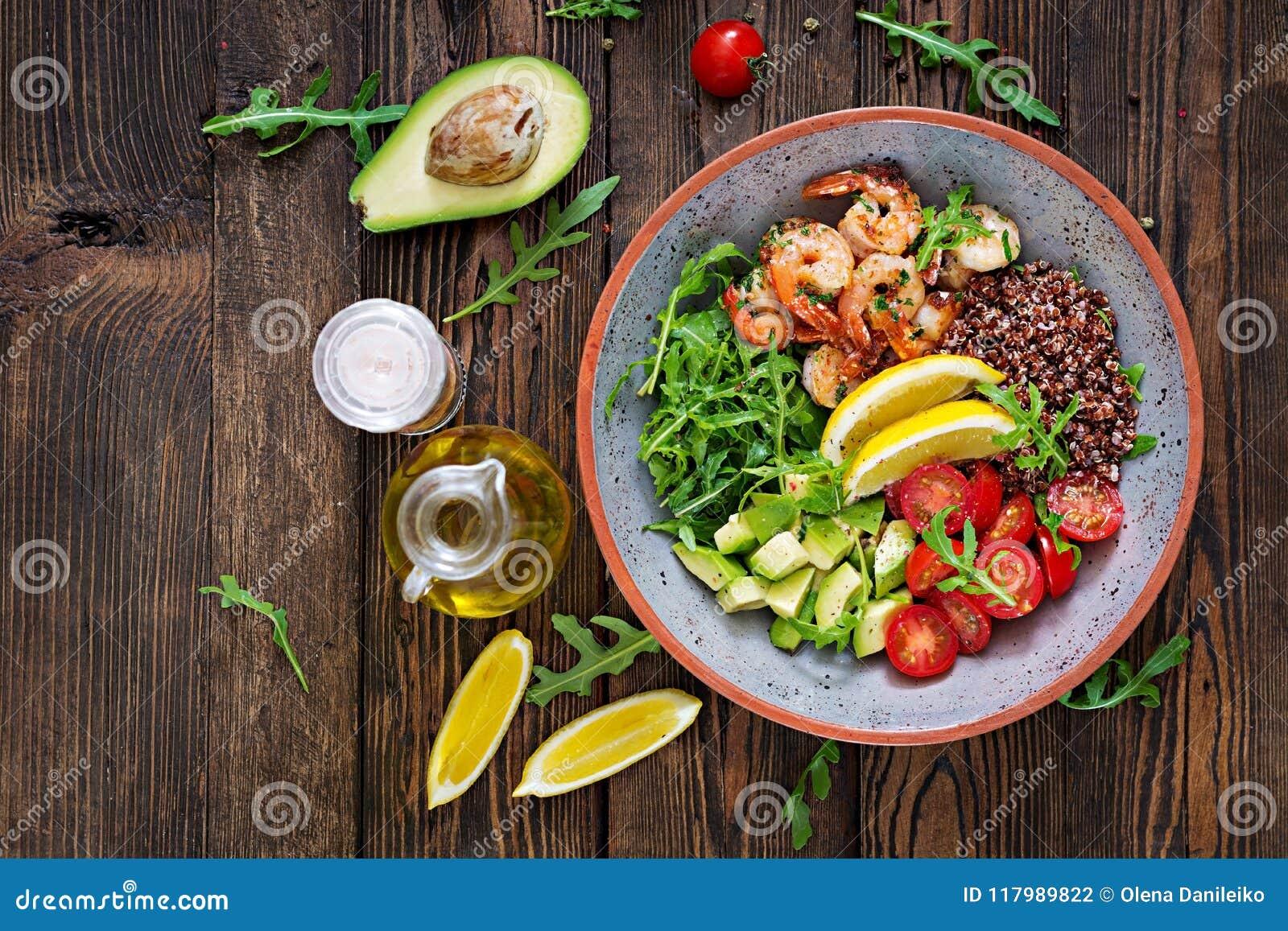 Buddha bowl with shrimps, tomato, avocado, quinoa, lemon and arugula