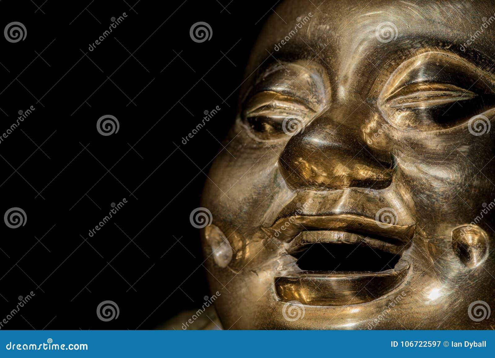 Buddha de bronze Cara de riso feliz da monge no close-up