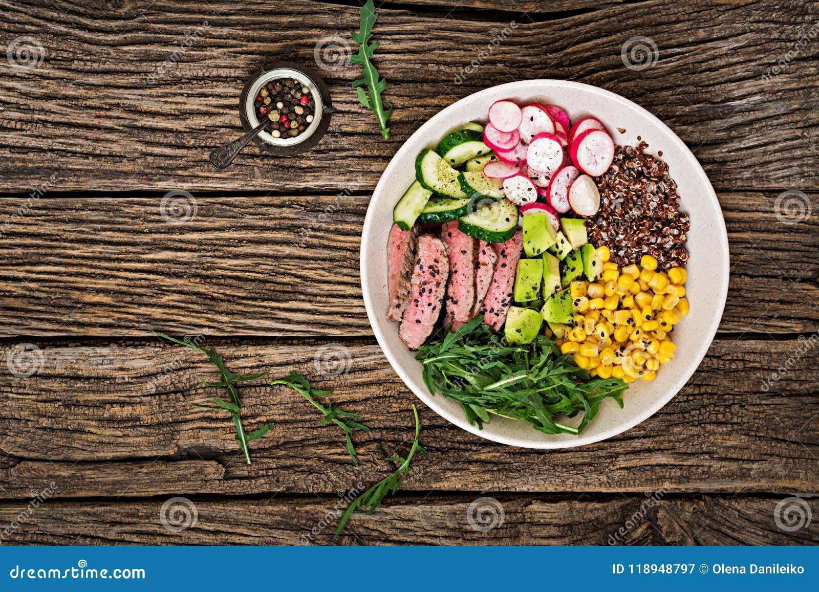 Buddha-Schüsselmittagessen mit gegrilltem Rindfleischsteak und Quinoa, Mais, Avocado, Gurke