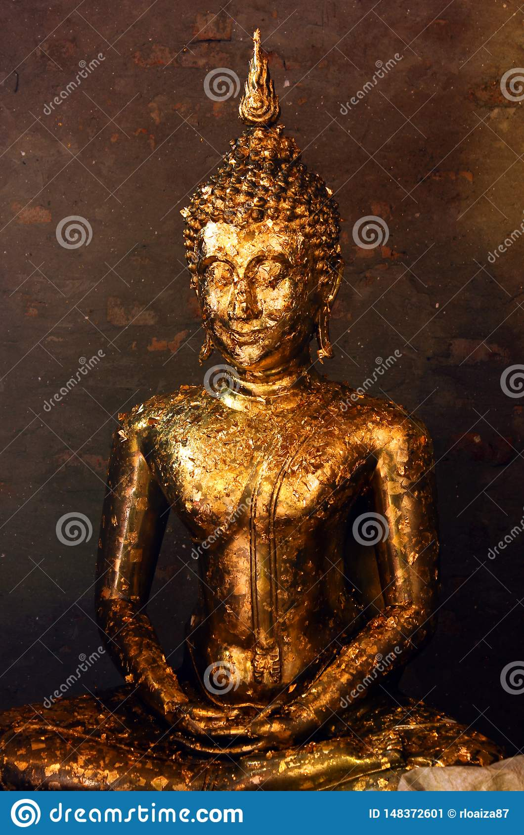 Buddha statue covered with offering of golden leaves wai phra at Wat Yai Chai Mongkhon temple in Ayutthaya, Thailand.