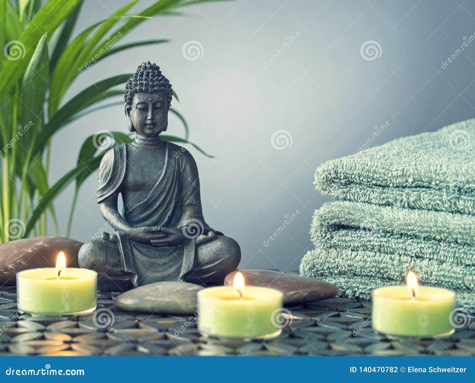 Buddha statua, ręczniki i świeczki,