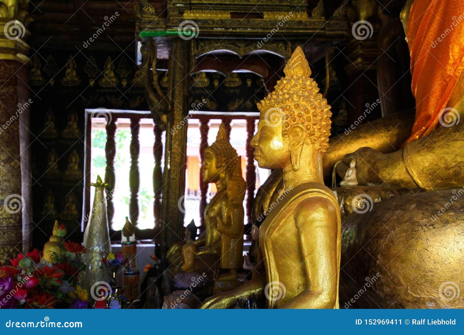LUANG PRABANG WAT XIENG THONG, LAOS - DECEMBER 17. 2017: Buddha statues inside temple illuminated by natural sunlight