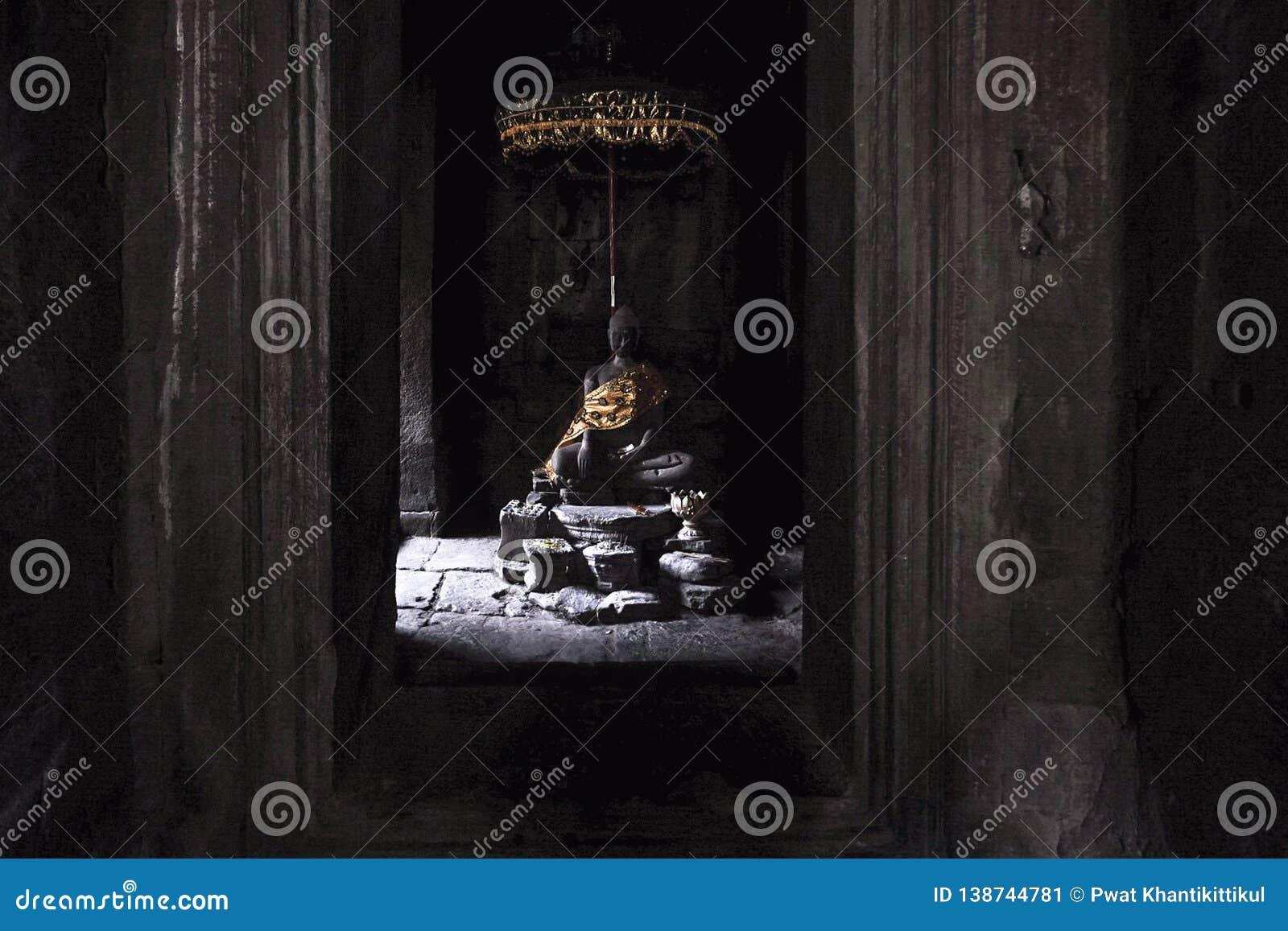 Buddhastaty som slås in i guld-, fortfarande lugna från morgonljuspasserandet till och med fönstret av den Bayon templet på Angko
