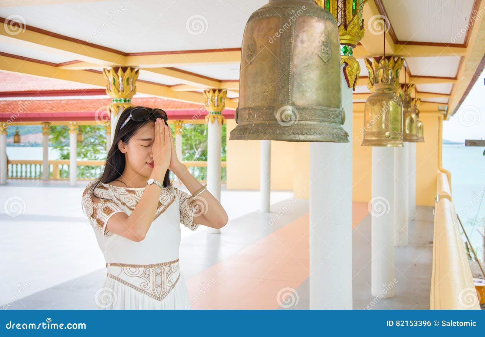 8aea2149d1 Buddhist girl praying inside the temple. Young buddhist girl praying inside  the temple royalty free