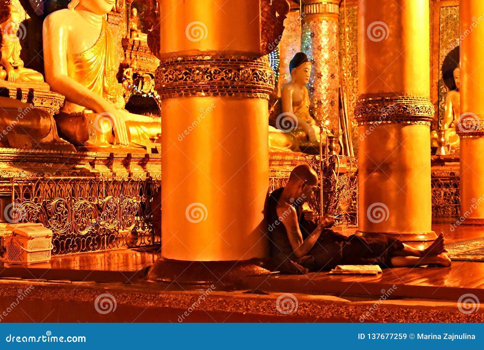 Buddhist Monk Checking His Smartphone at Shwedagon Pagoda in Yangon